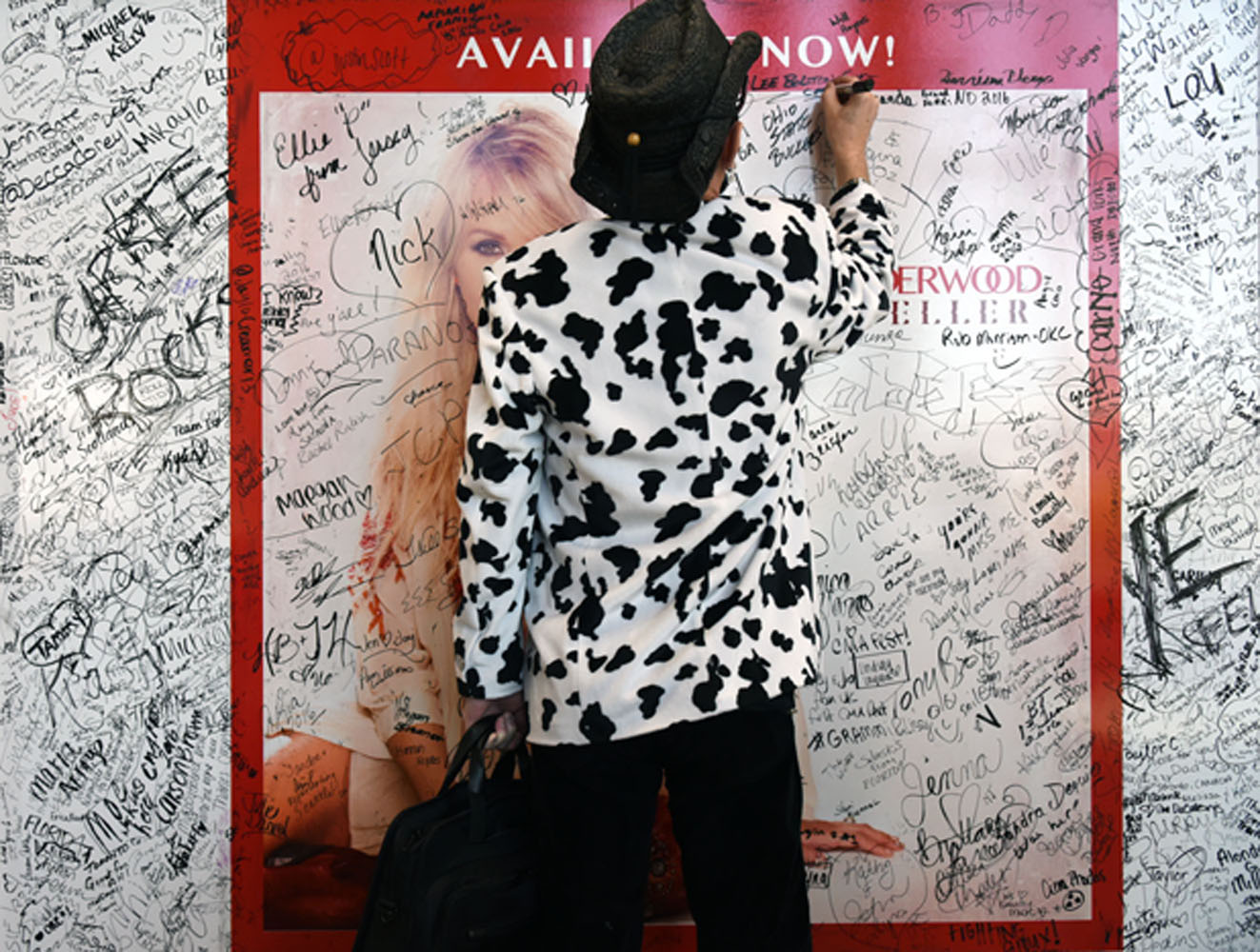 visitor signing poster at CMA festival in Nashville, 2015