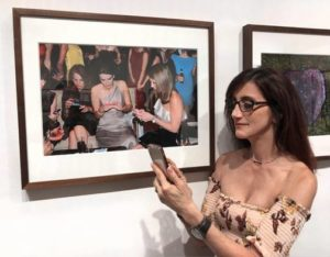 Person with cell phone next to an image of people with cell phones